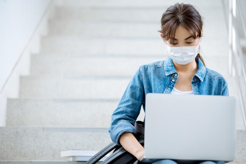 Student wearing COVID mask sitting on stairs at college with computer on her lap